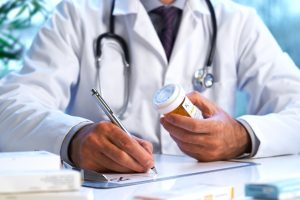 Doctor writing out RX prescription.