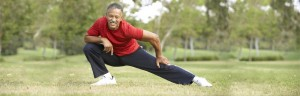 Senior Man Exercising In Park, Deep Knee Bend
